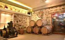 The area with the wooden barrels and the traditional machinery, preserves the memory of the traditional wine making process.