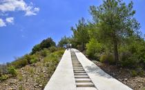 A concrete corridor, with steps and ramps, leads to the top of the trail.